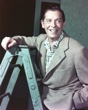 Milton Berle smiling on a Ladder