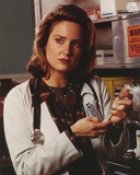 Sherry Stringfield Portrait in Medical Uniform and Brown Collar Shirt with Hands Holding a Syringe