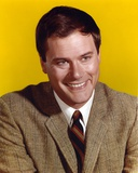 Larry Hagman smiling in Yellow Background