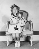 Shirley Temple sitting on Chair with a Doll in White Dress