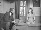 Anatomy Of A Murder Woman Talking to a Guy While sitting on the Sofa in a Movie Scene in Black and