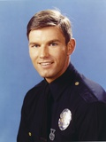 Adam-12 Posed in Police Officer Uniform with a Smile in a Portrait wish Blue Background