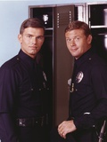 Adam-12 Posed in Police Uniform Looking at the Camera Near the Shelf in a Portrait