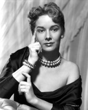 Vera Miles photographed waering a silk black  off-the-shoulder  boat neck gown  with her finger pre