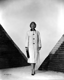 Vera Miles standing between two pyramids  wearing a three-buttoned jacket  holding a black purse an