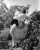 Vera Zorina leaning backwards with an outstretched arm on a vine covered rock  wearing shorts  and