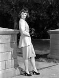 Alexis Smith Leaning on a Stone Fence wearing a Suit