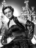 Alexis Smith sitting and wearing a Black Dress and Gloves