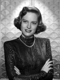 Alexis Smith Facing at the Camera wearing Black Long Sleeves and a Necklace