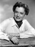 Alexis Smith Leaning on a Fence wearing White Long Sleeves