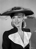 Carole Landis on a Hat and smiling