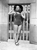 Betty Grable Posed with Hands on the Hat in Black Round Hat and One Piece Swimsuit with Black Flats
