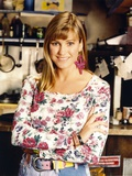 Cynthia Geary in a Floral Top smiling and standing Portrait