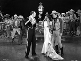 Bebe Daniels standing in White Long Dress while Two Men in Cowboy Outfit and Matador Outfit standin