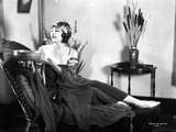 Betty Blythe sitting on the Reclining Bed in Strap Dress and Black Sheer Mufflers with Silk Headban