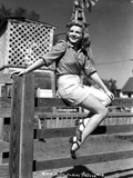 Claire Trevor sitting on Wood Fence with Heels