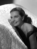 Cyd Charisse smiling in a White Couch wearing Black Sleeveless Dress and an Earrings