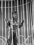Debbie Reynolds standing Behind Bars in Plaid Sleeves