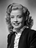 Gloria DeHaven Curly Hair smiling wearing Black Coat
