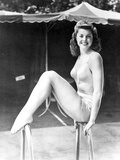 Esther Williams smiling and Seated in Swimsuit