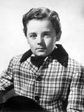 Freddie Bartholomew sitting on Side Boat in White Suit