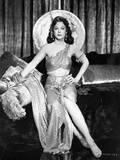 Hedy Lamarr sitting and wearing a Big Hat