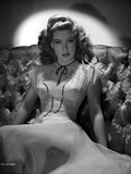 Gloria DeHaven sitting On A Couch in Gown in Black and White