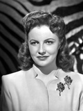 Joan Leslie on a Dress with Brooch and smiling