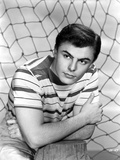 John Saxon wearing a Stripe Shirt while Leaning on a Wooden Post