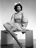 Jane Withers Seated on a Table in White Silk V-Neck Gathered Bodice with Bell Long Sleeve Dress wit