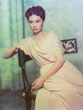 Jean Simmons sitting on a Chair in Beige Short Sleeve Draped Silk Dress