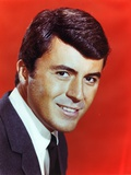 James Darren smiling in Black Linen Suit and White Collar Shirt on Red Background