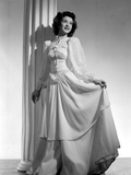 Jane Withers Posed in White Silk Keyhole-Neck Long Sleeve Dress with Left Hand Holding Skirt Up