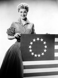 Jan Sterling Posed in Velvet Long Sleeve Dress and Accordion Pleated Skirt while Holding a Flag