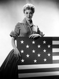 Jan Sterling Posed in Velvet Shirt and Pleated Skirt with Rolled Up Sleeves while Holding a Flag
