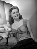 Joan Leslie on a Ruffled Top sitting on a Floor and smiling