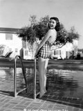 Jane Withers Posed in Gingham One Piece Swimsuit and Leaning Back while Hands Holding on the Metal