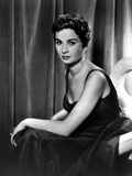 Jean Simmons Seated on a Couch in Black Velvet Strap Dress with Left Arm on the Lap