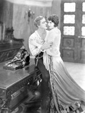 John Barrymore sitting on the Table while Holding on a Woman
