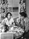 Merle Oberon sitting and smiling while Talking to a Man