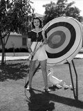 Jane Withers Posed in Black Short Sleeve Bodice and High Waist Short Skirt with Hands Holding a Bow
