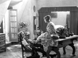 John Barrymore sitting on a Chair while the Woman is on the Table
