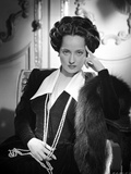 Merle Oberon sitting in Black Coat in Black and White