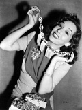 Lupe Velez smiling in Elegant Dress while Putting on Her Necklace