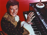 Liberace with Man Playing Piano in Red Background