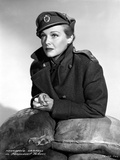 Madeleine Carroll Leaning on Sandbags  wearing Black Suit with Hat