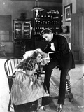 John Barrymore sitting on the Table and Accompanying an Old Lady