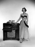 Jane Wyman Posed in White Silk Dress with Gathered Long Skirt with Right Hand on the Radio Box