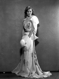 Margaret Sullivan standing in White Gown with Hat
