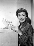 Jane Wyman Posed in Black Velvet Bishop Sleeve Poet Dress with Hands Holding A Glass Swan Figure